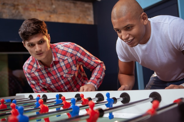 Group of friends playing table soccer at beer pub
