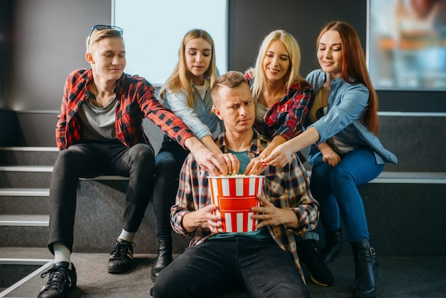 Group of friends poses with popcorn in cinema hall before the showtime. male and female youth waiting in movie theater, entertainment lifestyle
