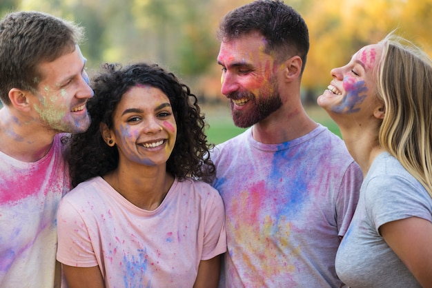 Group of friends posing covered in color