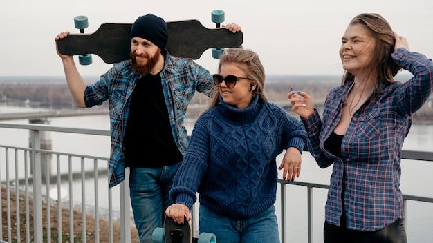 Gruppo di amici in posa insieme all'aperto con skateboard