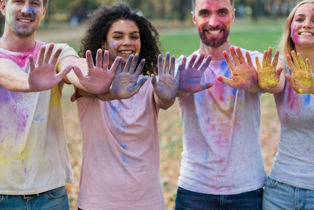 Group of friends posing with colored hands at holi