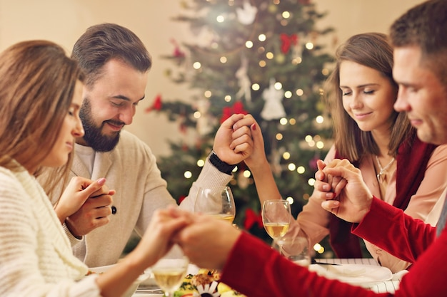 Group of friends praying over christmas table