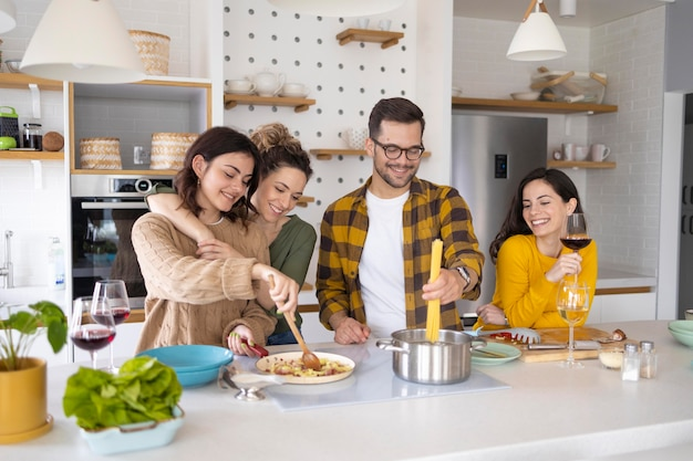 Group of friends preparing meal in the kitchen