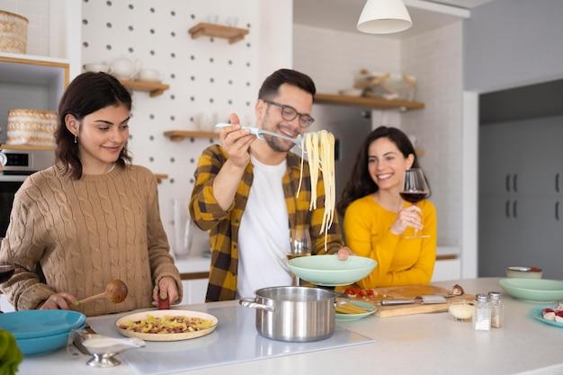 Gruppo di amici che preparano il pasto in cucina