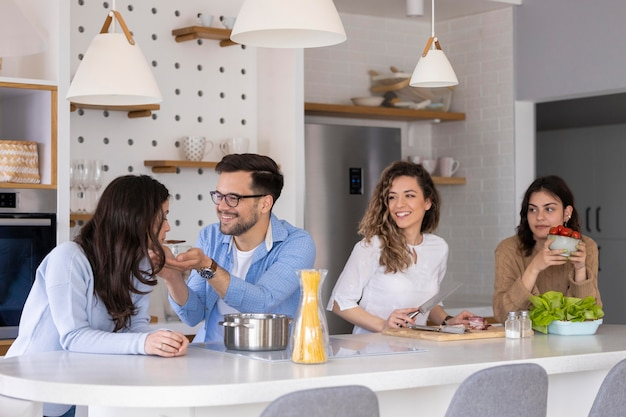 Group of friends preparing meal in the kitchen Free Photo