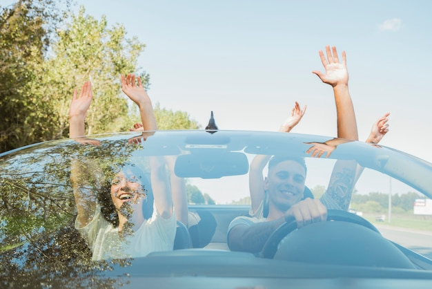 Group of friends raising arms in car