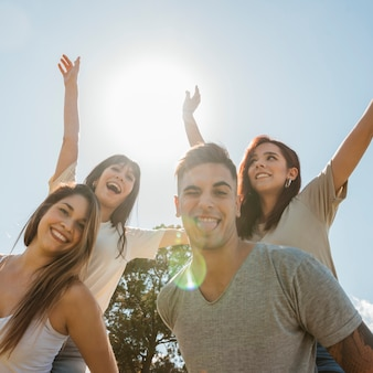 Group of friends raising arms on sky background