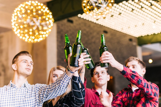 Group of friends raising the beer bottles in pub restaurant