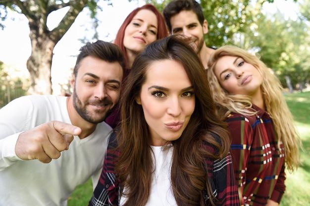 Gruppo di amici in un selfie con una ragazza in mezzo mettere bacio faccia