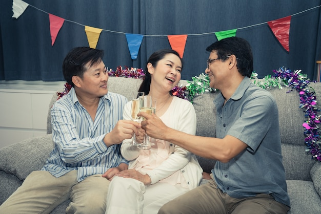 Group friends of senior man and woman happy party with champagne at home