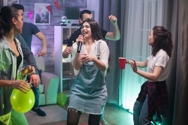 Gruppo di amici che cantano insieme alla festa. felice gruppo di persone.