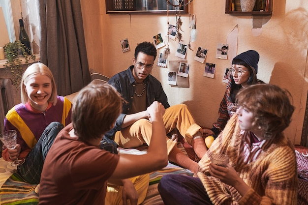Group of friends sitting on the floor drinking alcohol drinks and talking to each other during domestic party at home