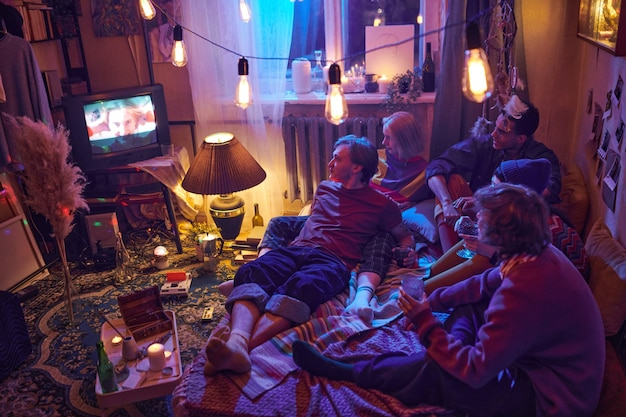 Group of friends sitting on the floor and watching tv in dark room decorated with lights during domestic party