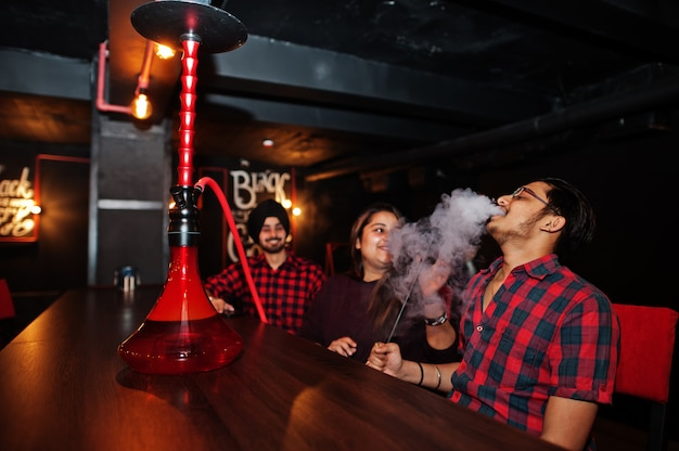 Group of friends sitting at lounge bar, smoke hookah and having rest