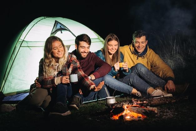 Group of friends sitting near bonfire