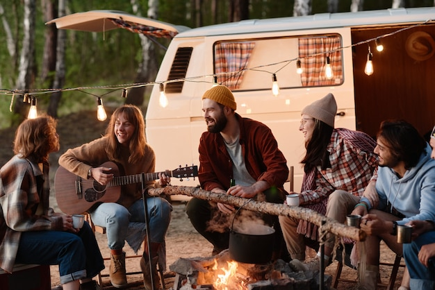Group of friends sitting near the fire and playing guitar together during picnic on the nature