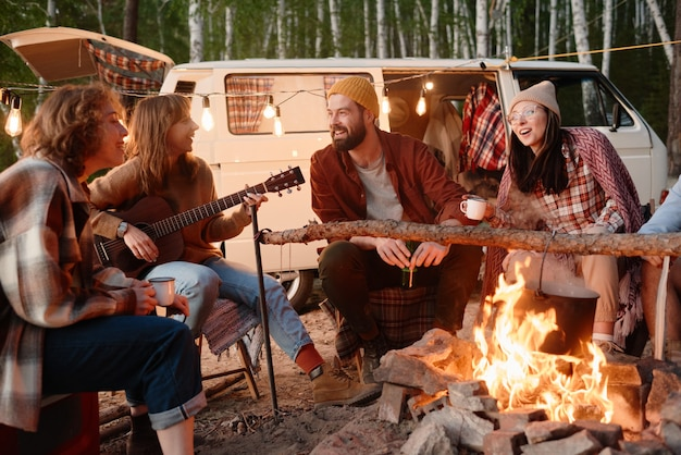 Group of friends sitting near the fire and singing songs with guitar during camping in the forest