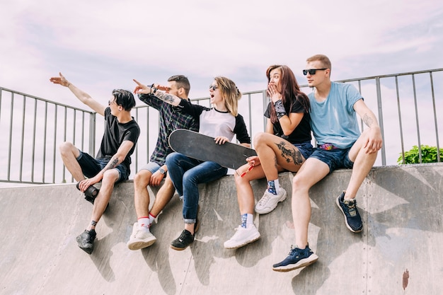 Group of friends sitting on ramp pointing at something