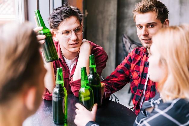 Group of friends sitting together holding green beer bottles