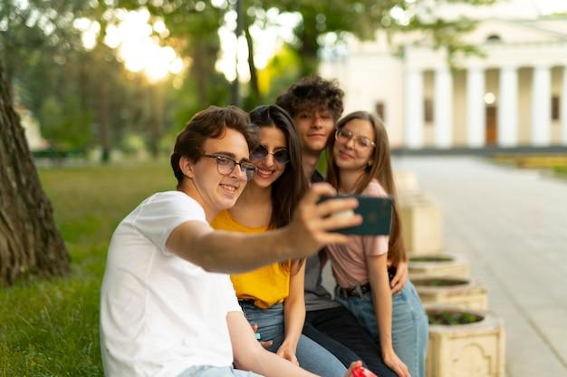 Gruppo di amici che trascorrono del tempo insieme all'aperto nel parco e si fanno selfie