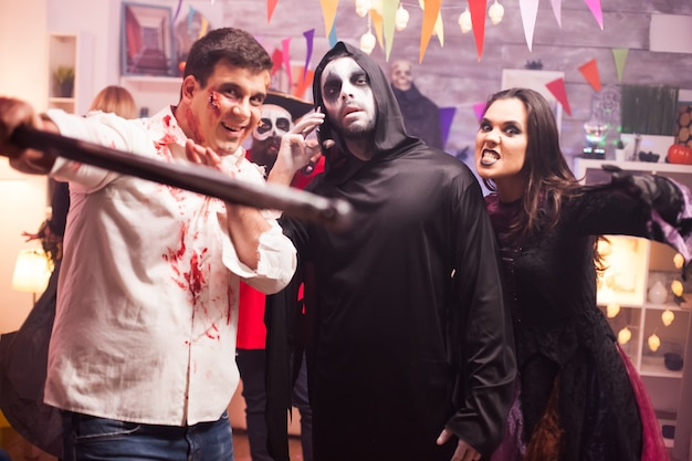 Group of friends in spooky costumes celebrating halloween. grim reaper using smartphone.