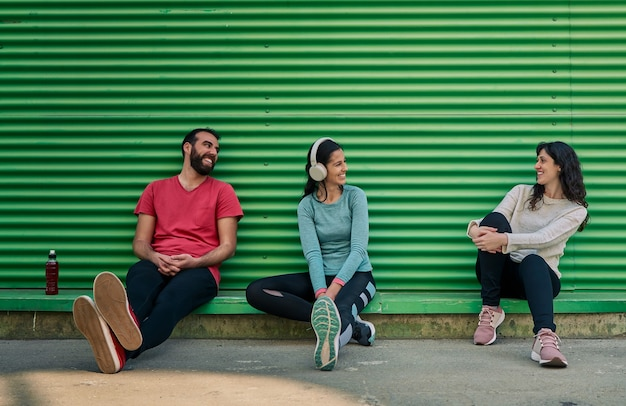 Group of friends in sportswear talking with a green background