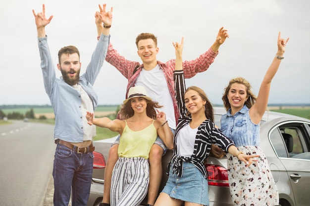 Group of friends standing in front of car raising hands gesturing