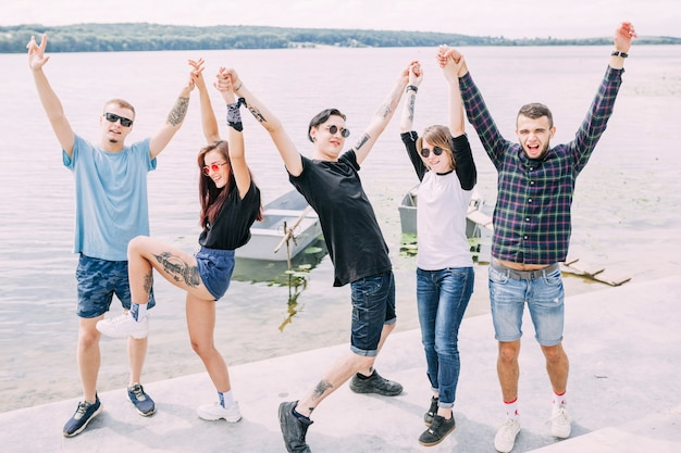 Group of friends standing near the lake raising their hands