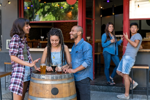 A group of friends standing outdoor at a brewery barrel while having drinks and fun talking.