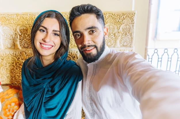 Gruppo di amici che prendono selfie nel ristorante arabo