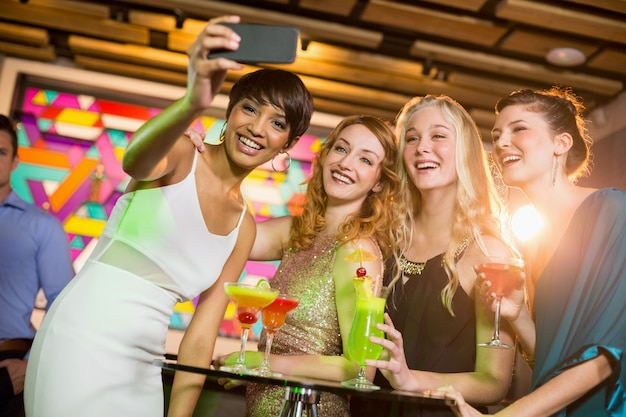 Group of friends taking selfie from mobile phone while having cocktail