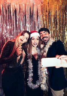 Gruppo di amici che prendono selfie su partiti di nuovi anni