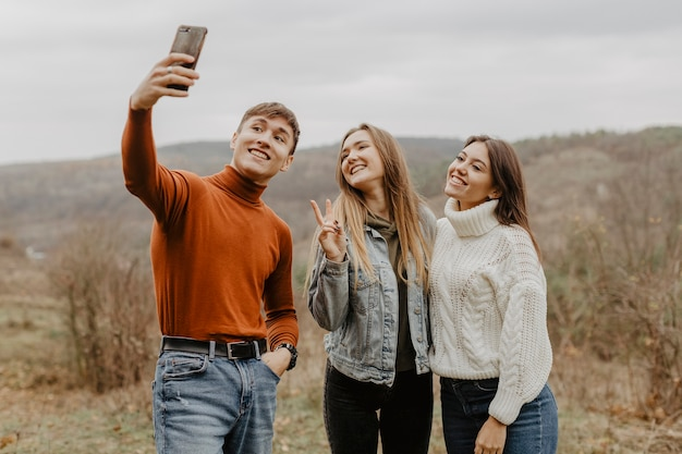 Group of friends taking selfies