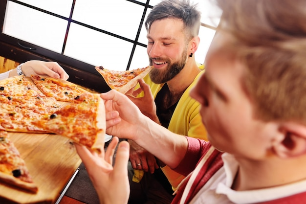 A group of friends talk and smile in a cafe and eat pizza.
