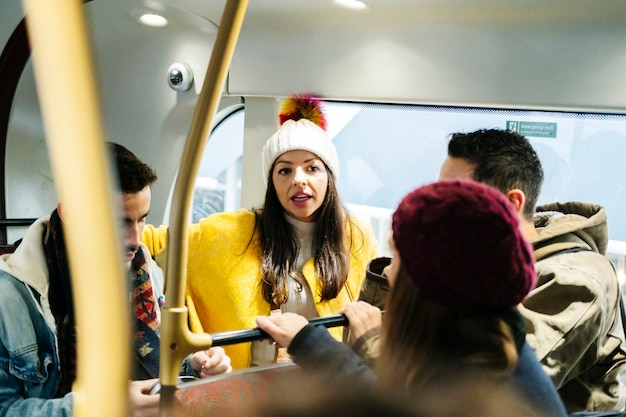 A group of friends talking travel in an urban bus