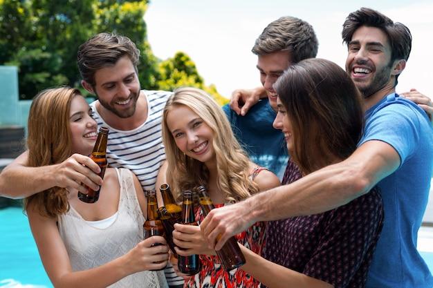 Group of friends toasting beer bottles near pool