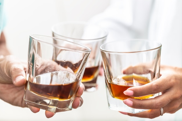 Group of friends toasting with glasses of whiskey brandy or rum indoors - closeup.