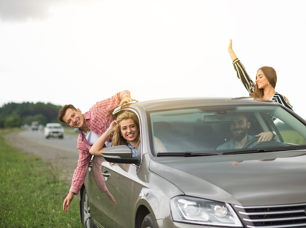 Group of friends travelling in the car hanging out through open window