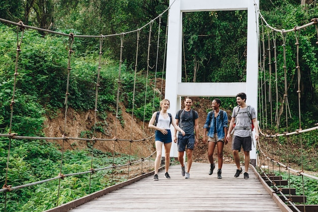 Group of friends walking on the bridge in a tropical countryside adventure and journey concept