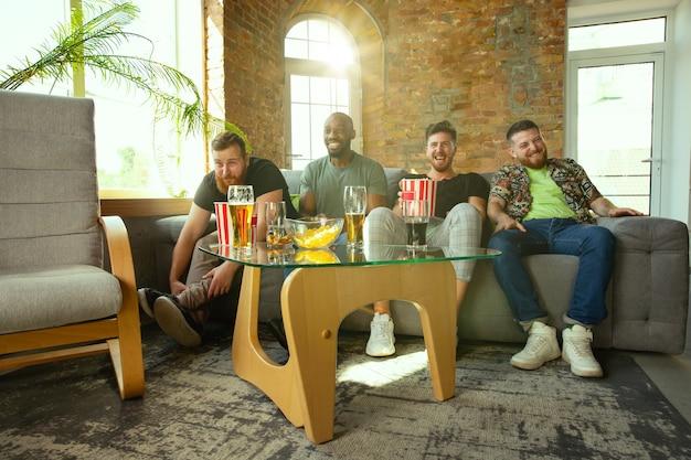 Gruppo di amici che guardano la partita in tv a casa. appassionati di sport che trascorrono del tempo e si divertono insieme