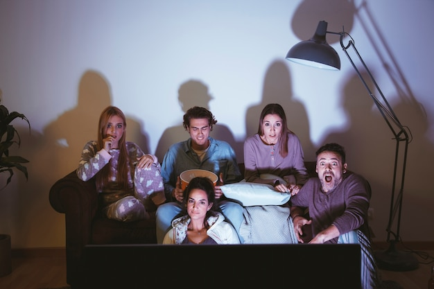 Group of friends watching a movie on couch