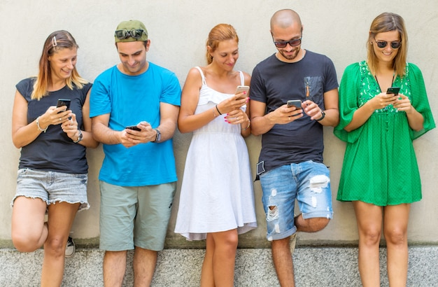 Group of  friends watching smart mobile phones - millennials generation