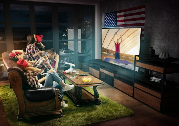 Group of friends watching tv, match, championship, sport games. emotional men and women cheering for favourite table tennis player in america with flag. concept of friendship, sport, competition.