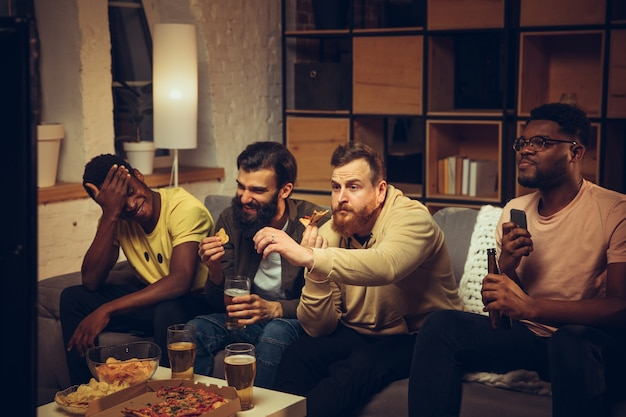Group of friends watching tv sport match together emotional fans cheering for favourite team watching on exciting game