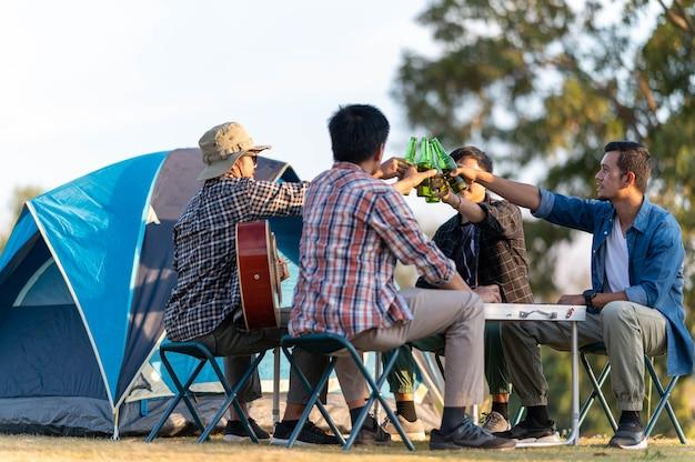 ビールとビールを飲みながらアコースティックギターを応援するグループの友達