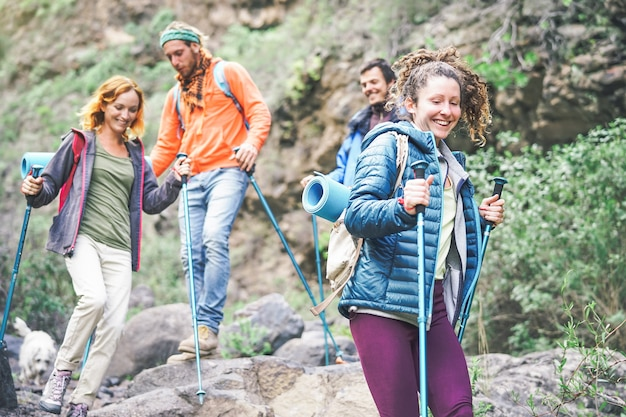 Group of friends with backpacks doing trekking excursion on mountain