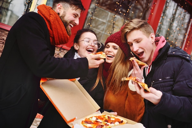 Group of friends with a box of pizza smiling and eating pizza on the street