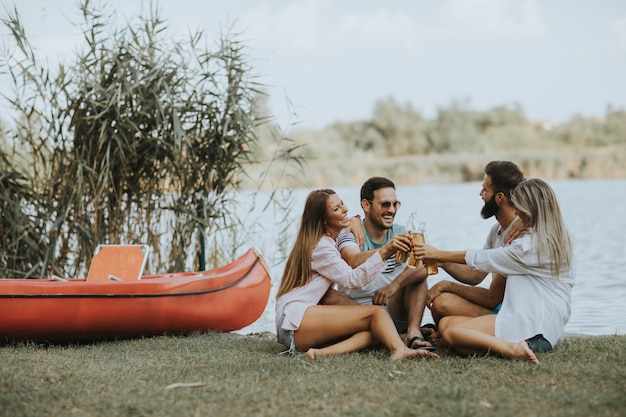 Group of friends with cider bottles sitting by the boat near the beautiful lake and having fun