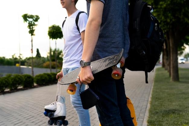 Gruppo di amici con lo skateboard in città