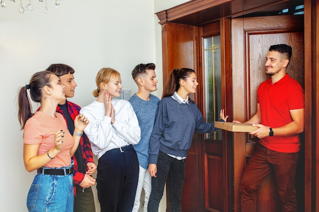 Group of friends young happy cheerful meet a smiling pizza delivery man at the door to the house